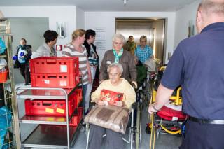 Ein Kommen und ein Gehen: Vor dem Aufzug im Altbau begegnen sich umziehende Bewohnerinnen und Bewohner, Mitarbeiter des Hauses Maria und Helfer des Rettungsdienstes. Foto: SMMP/Bock
